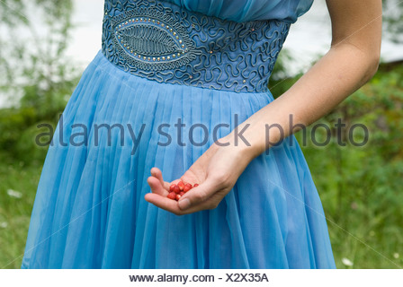 A woman holding wild strawberries in her hands. - Stock Photo