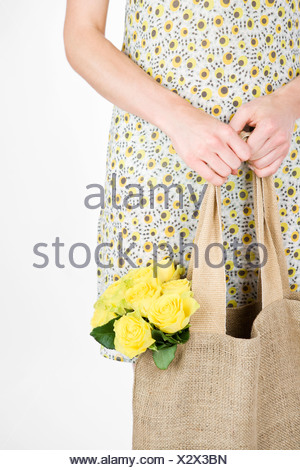 A Young Woman Carrying A Bunch Of Yellow Roses In A Shopping Bag - Stock Photo