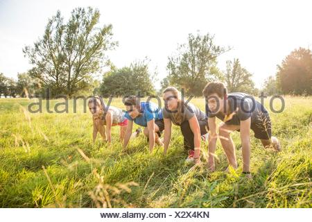 Group of friends in field, in starting position, about to race - Stock Photo