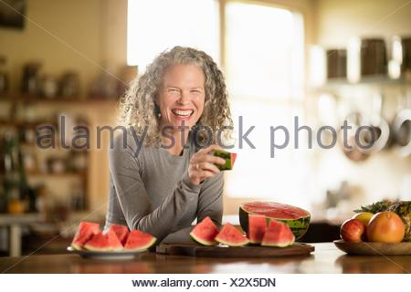 Portrait of mature woman eating watermelon in kitchen - Stock Photo