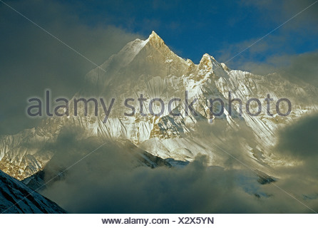 Clouds shroud sacred Mount Machhapuchhare (the 'Fish Tail'). - Stock Photo