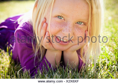 A young girl lying on the grass on her front with her chin resting on her hands. Laughing. Close up. - Stock Photo