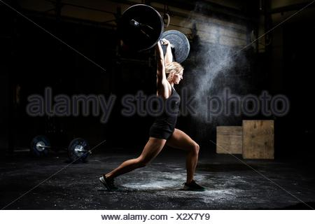 Side view of young woman weightlifting barbell in dark gym - Stock Photo