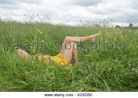 Woman lying in field showing legs - Stock Photo