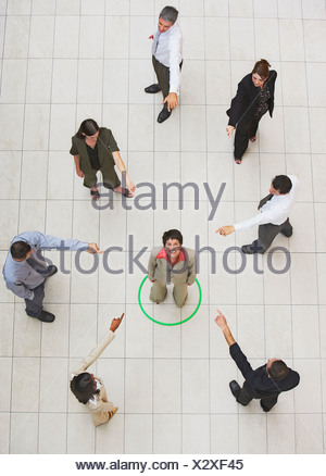 Aerial View of businesswoman standing in circle with businesspeople pointing - Stock Photo