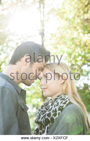 Couple nuzzling each other outdoors - Stock Photo