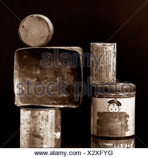 Old tin cans and boxes stacked on top of each other - Stock Photo