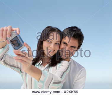 A couple taking pictures outdoors - Stock Photo