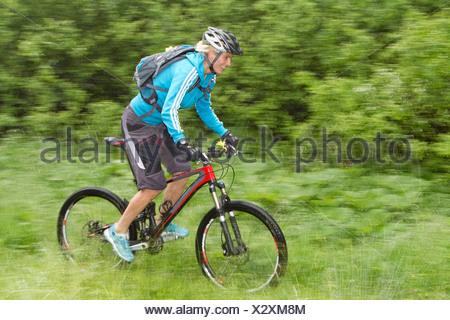 Germany, Bavaria, Schliersee, Mid adult woman moutainbiking in rain - Stock Photo