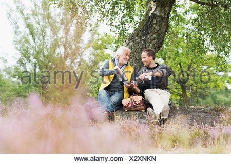 Father and adult son drinking coffee from flask - Stock Photo