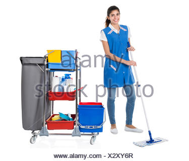 Happy Female Janitor Mopping By Trolley On White Background - Stock Photo