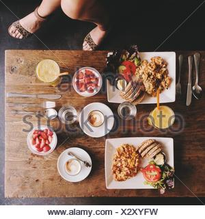 Overhead view of woman's legs and breakfast table - Stock Photo