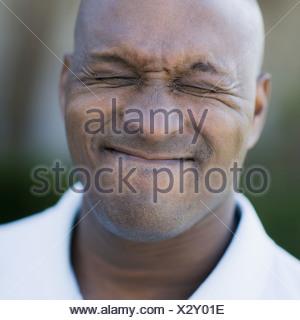 Portrait of man grimacing, close-up - Stock Photo