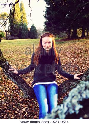 Portrait Of Happy Young Woman Sitting On Branch In Park - Stock Photo