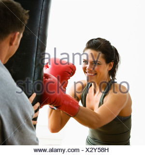 Woman wearing boxing gloves hitting training mits man is holding - Stock Photo