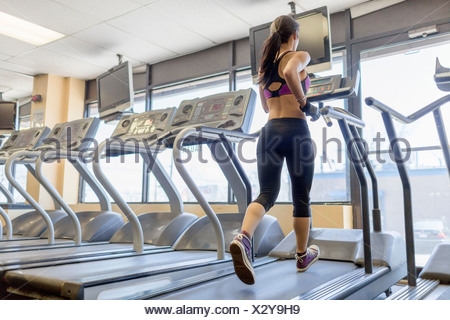 Mid adult woman running on treadmill in gym - Stock Photo