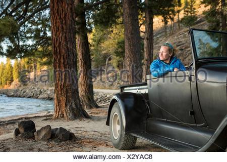 Woman sitting in renovated truck watching sunset, Payette Lake, McCall, Idaho, USA - Stock Photo