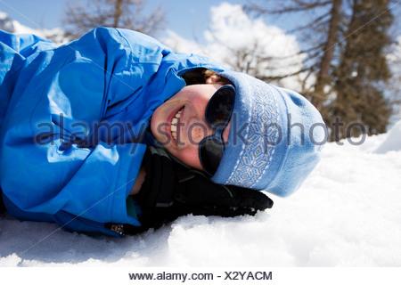 Girl in blue lying in snow. - Stock Photo