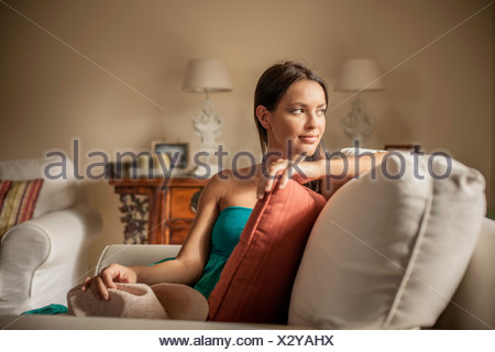 Young contemplative woman sitting in armchair - Stock Photo