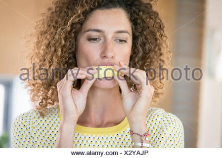 Young woman eating a slice of pineapple - Stock Photo