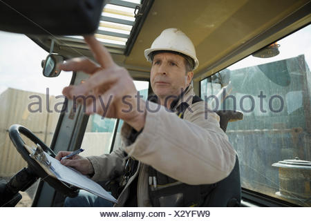 Male forklift driver with clipboard inside forklift in container yard - Stock Photo