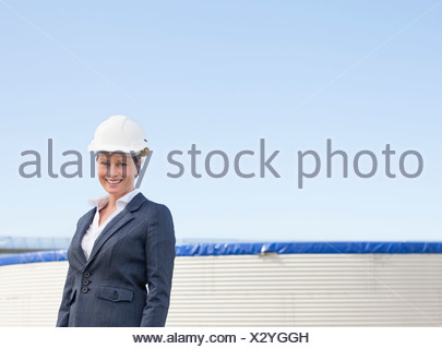 Businesswoman in hard hat walking outdoors - Stock Photo