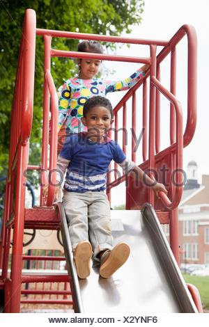 Boy and friends sliding on playground slide - Stock Photo