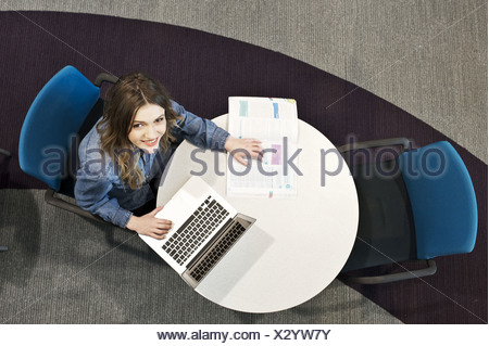 Young woman sitting at table using laptop, high angle - Stock Photo