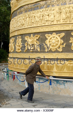 Tibetan Buddhism, Tibetan man, believer turning a giant prayer wheel, Zhongdian, Shangri-La, Yunnan Province, People's Republic - Stock Photo