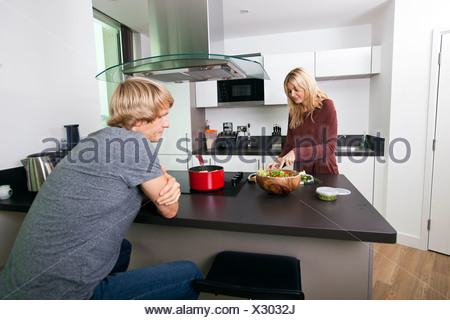 Man looking at woman cutting vegetable in kitchen - Stock Photo