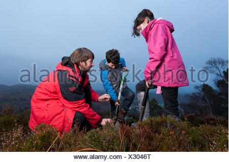 Children from Lochinver primary school being shown how to plant trees on moorland at Culag Wood, Sutherland, Highlands, Scotland - Stock Photo