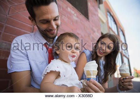Father holding daughter with messy ice cream face - Stock Photo
