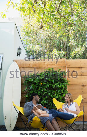 Relaxed couple talking and drinking wine on patio - Stock Photo
