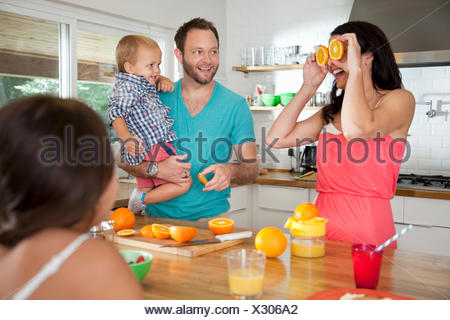 Mother making a face with oranges for her family at breakfast bar - Stock Photo