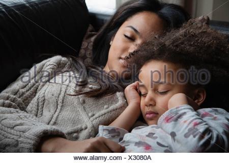 Two sisters asleep on sofa - Stock Photo