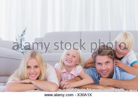 Smiling family lying on the carpet Stock Photo