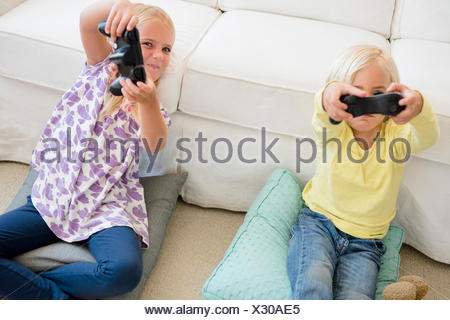 Boy (4-5) and girl (6-7) playing video game - Stock Photo