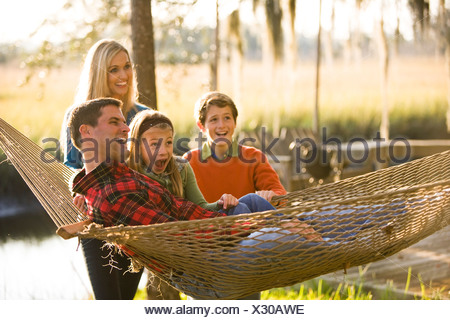 Family having fun outdoors on hammock - Stock Photo