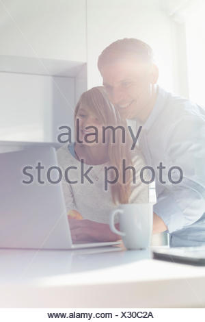 Father and daughter using laptop at home - Stock Photo