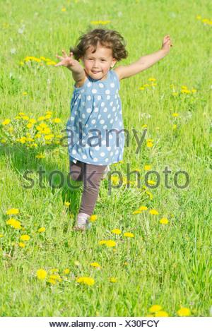 Little girl running in meadow - Stock Photo