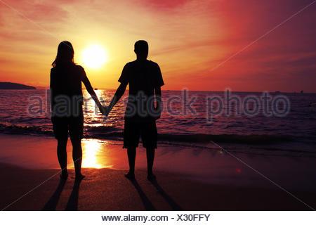 Full Length Of Silhouette Couple Standing On Beach Against Orange Sky