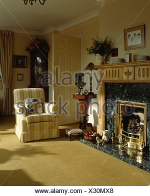 Fireplace and striped armchair in sittingroom with mustard yellow carpet - Stock Photo
