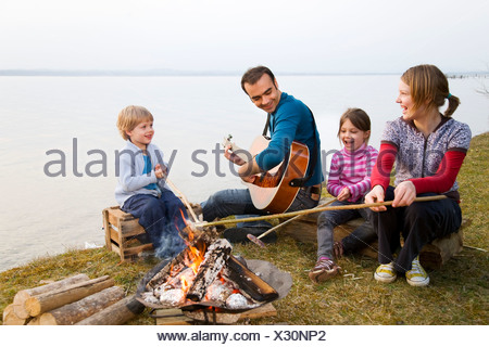 two girls, boy and man roasting sausages - Stock Photo
