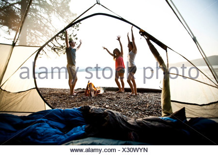 Three young adults smiling and dancing around a camp fire on a camping and kayaking trip on a lake in Idaho. - Stock Photo