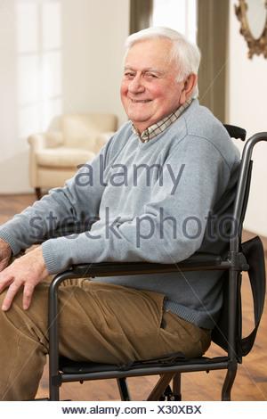 Disabled Senior Man Sitting In Wheelchair - Stock Photo