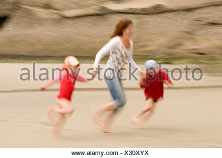 New Zealand, Cape Farewell, Woman with children (4-5) (6-7) on the beach, having fun - Stock Photo
