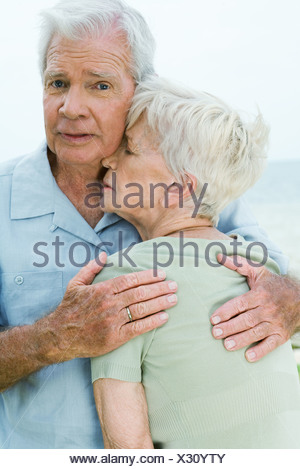 Senior couple, man holding woman tightly against him, looking at camera - Stock Photo