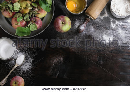 Ingredients for making apple cake. Flour, sugar, broken egg in tin cans, fresh apples with leaves in metal plate, vintage spoon - Stock Photo