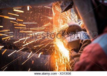 Metal grinding in repair works in surface coal mine - Stock Photo