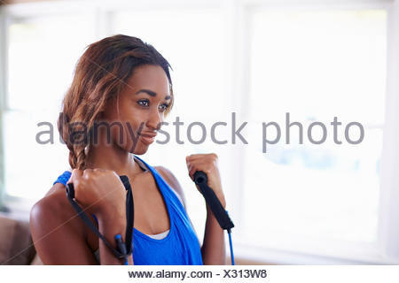 Young woman exercising in sitting room - Stock Photo